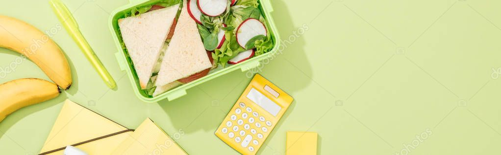 Panoramic shot of lunch box with food near office supplies