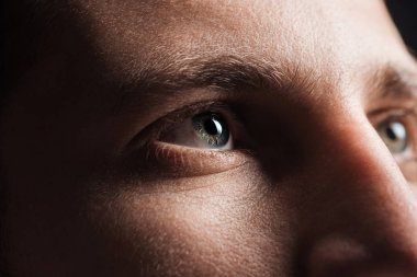 close up view of adult man looking away in darkness