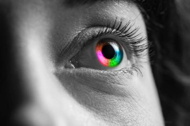 black and white shot of human with rainbow colors eye