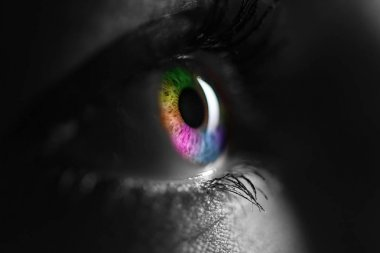 black and white shot of human with bright rainbow colors eye