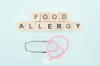 Top view of wooden blocks with food allergy lettering near stethoscope isolated on blue stock vector