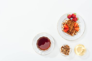 top view of waffle with strawberries on plate near cup with tea, bowls with honey and nuts on white