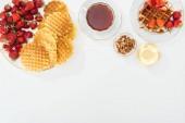Nejlepší pohled na wafle, jahody, med, ořechy a čaj na bílém