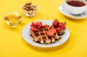 snídaně s vaflí a jahody pokovené, med, ořechy a čaj na žlutém pozadí