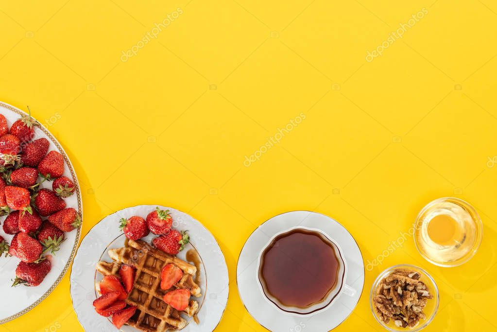 Top view of plates with strawberries and waffles with cup of tea and bowl with nuts and honey on yellow stock vector