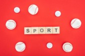 Fotografie sport lettering on wooden cubes near softballs isolated on red