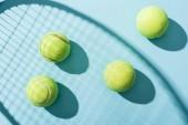 pohled na tenisky v blízkosti stínu tenisového Bušku na modrém