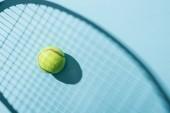 pohled na tenisovou kouli v blízkosti stínu tenisového Bušku na modrém