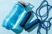 Photo close up of sport bottle with water near skipping rope on blue