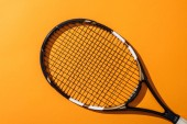 top view of black tennis racket on yellow