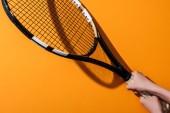 oříznutý pohled na sportivní ženu držící tenisový randál na žluté