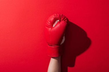 Cropped view of woman in leather boxing glove on red stock vector