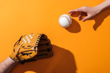 cropped view of man in brown baseball glove near softball and woman on yellow