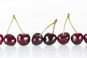 red, fresh, whole and sweet cherries on white background with copy space