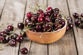 red, fresh, whole and ripe cherries on bowl on wooden surface