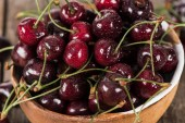 vörös, friss, teljes és érett cseresznye cseppcskével, fa asztallal