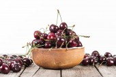 Fotografie red, fresh, whole and ripe cherries covered with droplets on bowl on wooden table