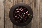 top view of red, fresh, whole and ripe cherries on bowl on wooden surface