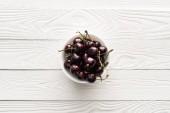 friss, édes és érett cseresznye felsõ nézete a tálon fa háttérrel