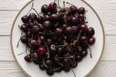 friss, édes és érett cseresznye felülnézete cseppeket tartalmazó fehér lemezen
