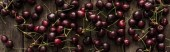 panoramic shot of fresh, sweet, red and ripe cherries covered with water drops on wooden table