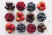 Fotografie pohled na celé brusinky, jahody, borůvky a třešně v plastových kelímcích