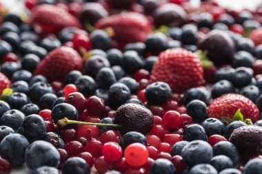 selective focus of red, fresh and ripe cranberries, strawberries, blueberries and wet cherries