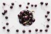 top view of sweet and fresh cherries covered with water drops on bowl