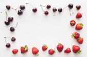 vista dallalto delle ciliegie dolci e fresche ricoperte di gocce dacqua e fragole rosse su sfondo bianco