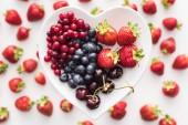 Fényképek top view of sweet cranberries, blueberries, strawberries and cherries on heart shaped plate