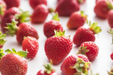selective focus of sweet and red strawberries on white background