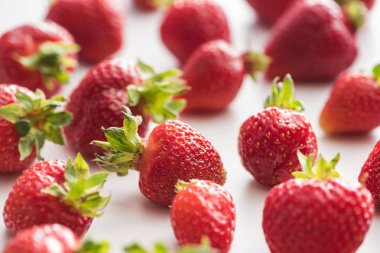 selective focus of whole and red strawberries on white background