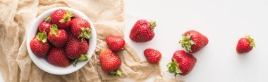 panoramic shot of fresh and ripe strawberries on white bowl with cloth