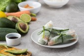 tasty spring rolls on white plate among raw ingredients