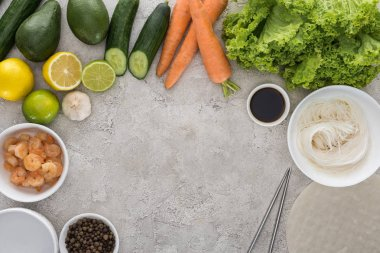 top view of lemons, limes, avocados, carrots, black pepper, shrimps, soy sauce, rice paper, garlic,noodles and lettuce on table