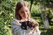 Fotografie glückliches blondes Mädchen hält süße walisische Corgi-Welpen im Garten neben grünem Baum