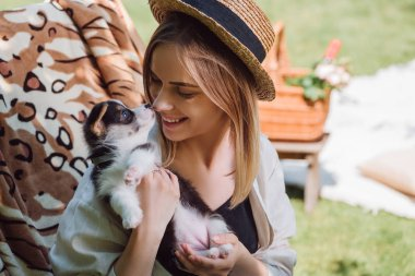 happy blonde girl in straw hat looking at puppy while sitting in deck chair in garden