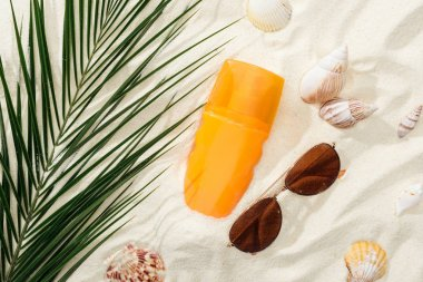 orange bottle of sunscreen on sand with seashells, green palm leaf and stylish sunglasses