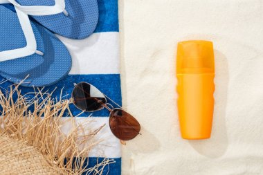 Top view of sunscreen, straw hat, flip flops, sunglasses and striped blue and white towel on golden sand stock vector