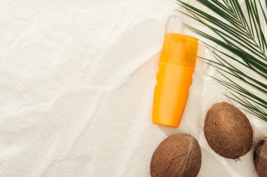 top view of palm leaf, coconuts and orange sunscreen on sand