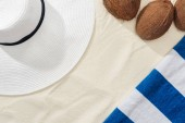 top view of coconuts, striped towel and white straw hat on sand