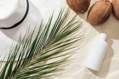 top view of palm leaf, sunscreen, coconuts and white straw hat on sand