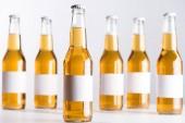 messa a fuoco selettiva di bottiglie di birra di vetro con etichette bianche bianche vuote isolate sul grigio