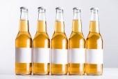 pět pivních lahví s prázdnými bílými štítky izolované na šedé