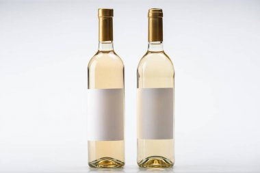 two bottles of white wine with blank labels on white background