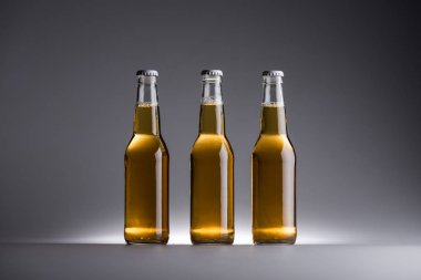 Three glass bottles with beer in row on grey background stock vector