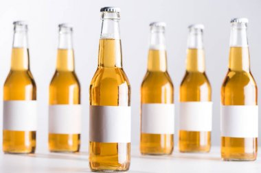 Selective focus of glass beer bottles with blank white labels isolated on grey stock vector