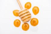 pohled na kapky medu a dřevěný med naběračka izolovaný na bílém