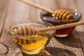 selektivní zaměření skleniček s medem a medovníky na dřevěném stolku na slunci