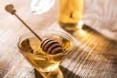 skleněná nádobka s medu a naběračka na dřevěném stolku na slunci
